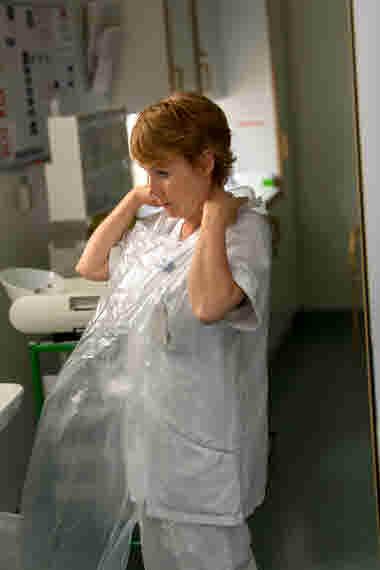 Barnmorska tar på sig förkläde av plast på förlossningen på länssjukhuset i Kalmar.