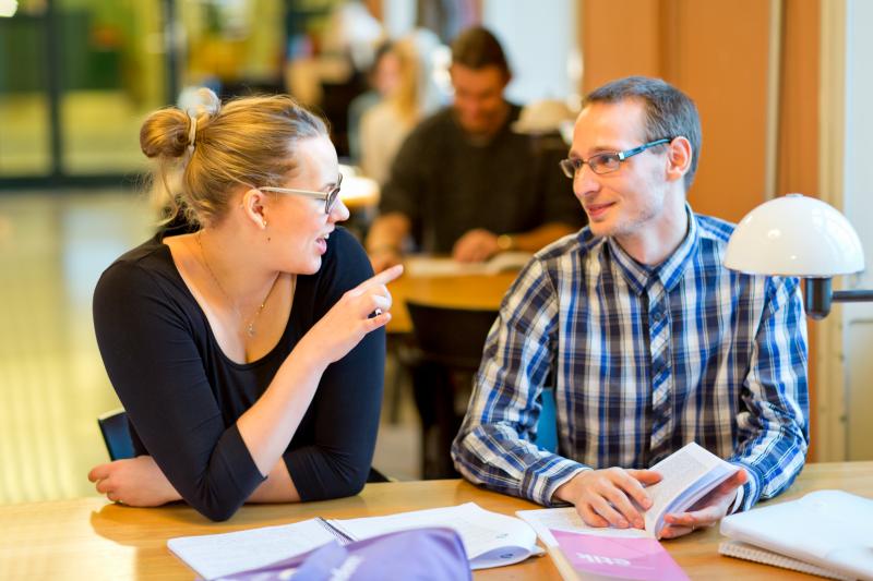 Två studenter sitter vid ett bord och pratar på ett bibliotek.