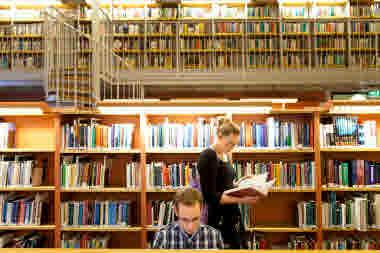 Två studenter på bibliotek. En står upp och läser i en bok, den andra sitter ner.
