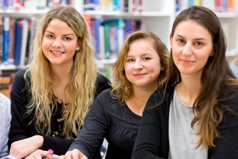 Tre glada studenter på bibliotek
