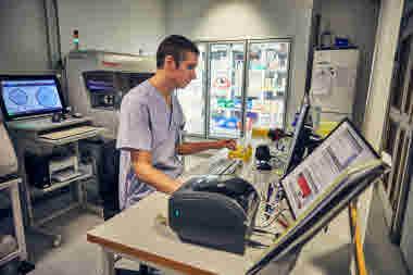 Biomedicinsk analytiker på Gävle sjukhus mars 2021. BMA man sitter vid datorn allvarlig neutral min maskiner utrustning