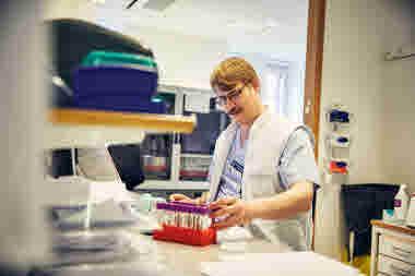 Biomedicinsk analytiker på Gävle sjukhus mars 2021. BMA sitter vid skrivbord och arbetar. Man och förtroendevald med mustasch