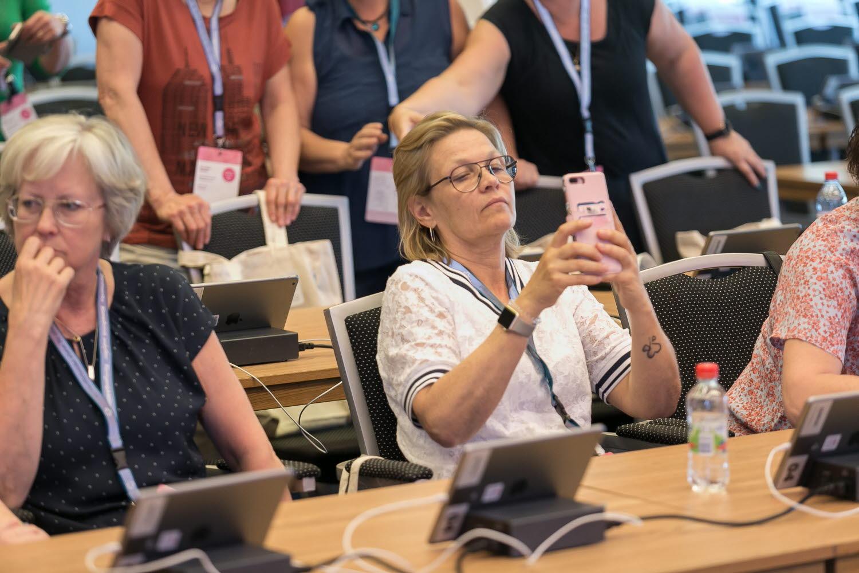 Paus under kongressen 2018. Ett kongressombud tar en bild med sin smartphone.
