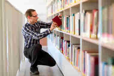 Student letar bok bland hyllorna på ett bibliotek.