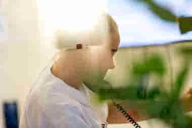 Barnmorska som pratar i telefon på förlossningen på länssjukhuset i Kalmar. Barnmorskan håller fast telefonluren mellan axeln och örat.