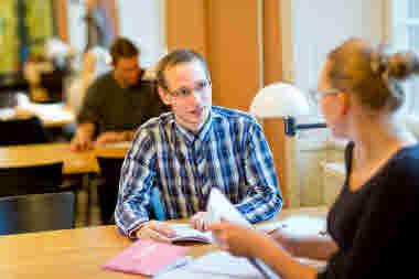 Student sitter vid ett bord på bibliotek tillsammans med en annan student
