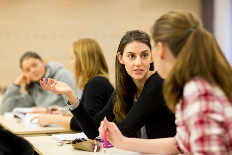 Studenter i klassrumsmiljö. Seriösa samtal. Till Vårdförbundet Student.