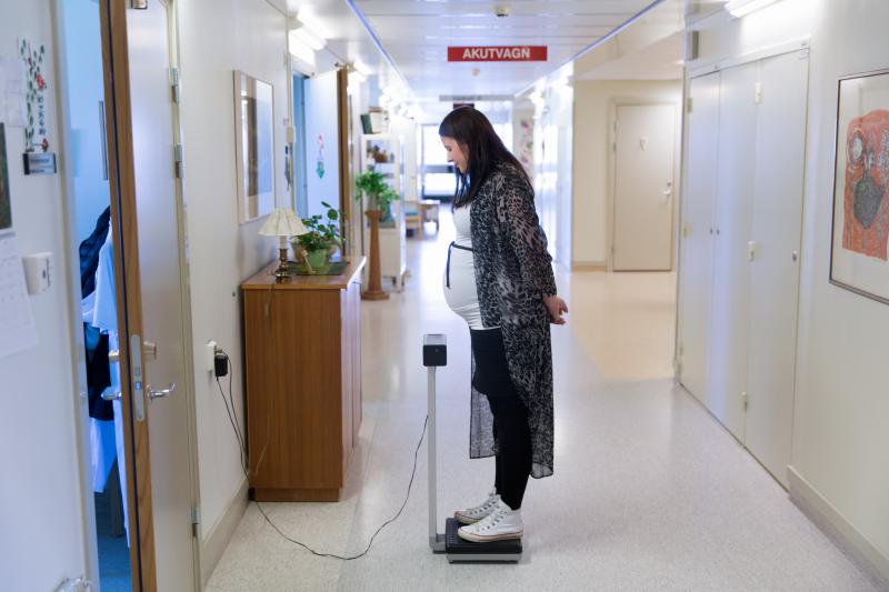 Kvinnokliniken Kullbergska sjukhuset Katrineholm. Gravid kvinna väger sig på en våg i korridoren