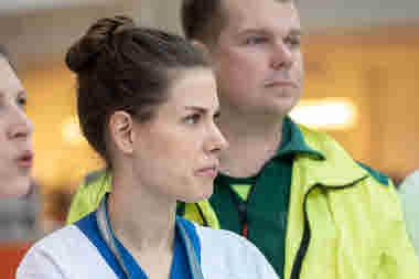 Två förtroendevalda med allvarlig min tittar åt höger. Kvinna man. Ambulans. Fotade i Uppsala.
