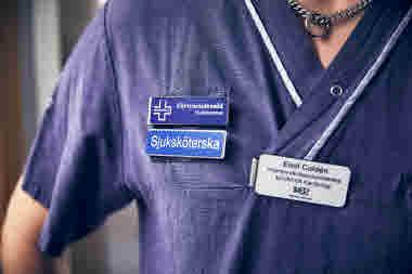 Förtroendevald på intensivvårdsavdelningen på MIVA SÖS i januari 2021. Covid-19, corona, intensivvård, sjuksköterska, intensivvårdssjuksköterska, namnskylt, närbild, blå,