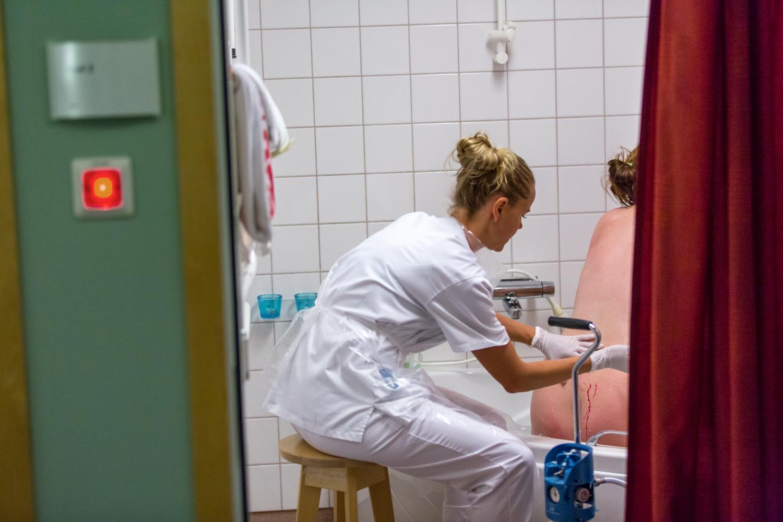 Barnmorska tillsammans med gravid kvinna innan förlossning. Barnmorskan förbereder kvinnan som sitter med ryggen mot kameran.