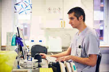 Biomedicinsk analytiker på Gävle sjukhus mars 2021. BMA man sitter vid datorn allvarlig neutral min