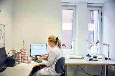 Biomedicinsk analytiker på Gävle sjukhus mars 2021.  BMA sitter vid skrivbord och analyserar odlingar av urinvägsinfektion. Kontor arbete