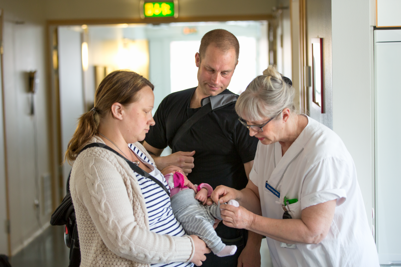 Nyblivna föräldrar med bebis tillsammans med barnmorska på förlossningen på länssjukhuset i Kalmar