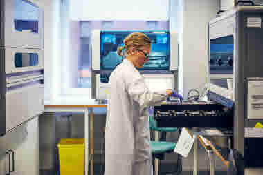 Biomedicinsk analytiker på Gävle sjukhus mars 2021.  BMA laddar maskin med prover.