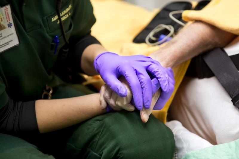 Ambulanssjuksköterska håller patient i handen. Ambulanssjuksköterskan har lila handskar på sig.